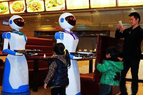 游客在玻璃钢送餐机器人雕塑前合影